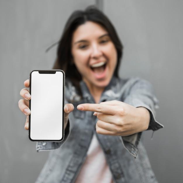 Zdziwiona młoda kobieta pokazuje smartphone Darmowe Zdjęcia
