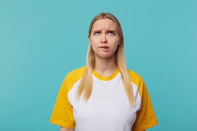 Zdziwiona Młoda Niebieskooka Blond Kobieta O Długich Włosach Marszczy Brwi I Patrzy W Zamyśleniu W Górę, Stojąc Na Niebieskim Tle Z Opuszczonymi Rękami Darmowe Zdjęcia
