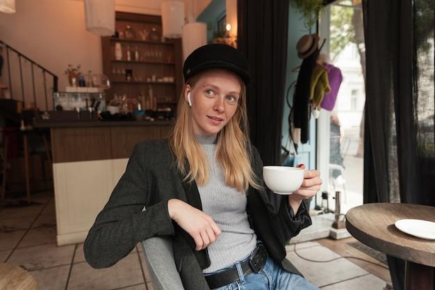Zdziwiona Młoda śliczna, Długowłosa Blondynka Siedzi Przy Stole W Miejskiej Kawiarni I Pije Herbatę, Ma Na Sobie Słuchawki I Modne Ciepłe Ubrania Darmowe Zdjęcia