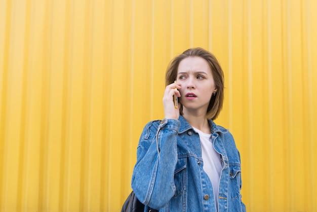 Zdziwiona Piękna Dziewczyna Opowiada Na Telefonie Na Tle Kolor żółty ściany I Patrzeje Z Ukosa. Premium Zdjęcia