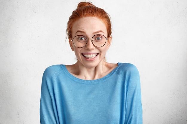Zdziwiona Piękna, Uszczęśliwiona Modelka O Rudych Włosach I Piegowatej Skórze, Nosi Swobodny Niebieski Sweter, Zaskakująco Patrzy Przez Okrągłe Okulary Darmowe Zdjęcia