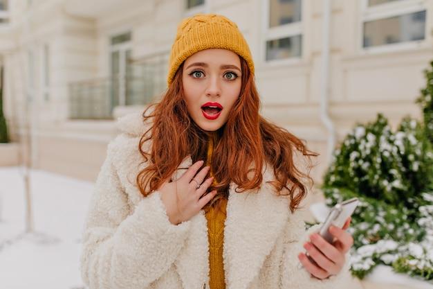 Zdziwiona Ruda Dziewczyna Stojąca Na Ulicy W Zimny Dzień. Wspaniała Młoda Kobieta Z Telefonem Pozowanie Na świeżym Powietrzu. Darmowe Zdjęcia
