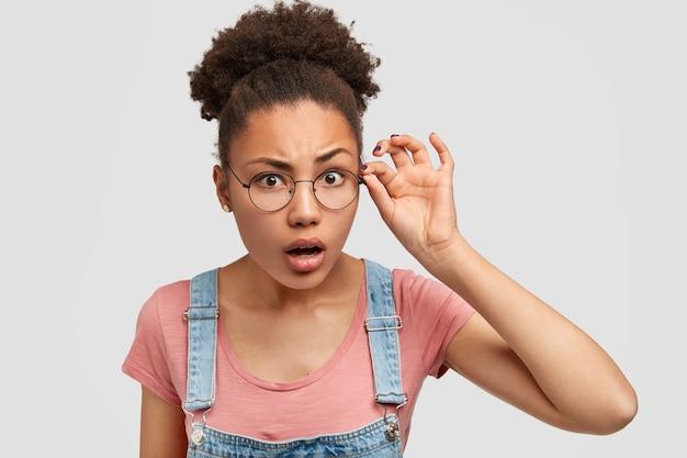 Zdziwiona, Zaskoczona Ciemnoskóra Młoda Kobieta Skrupulatnie Patrzy Przez Okrągłe Okulary, Ma Kręcone, Czarne Włosy Zaczesane W Kok, Bacznie Na Coś Patrzy, Nosi Dżinsowe Ogrodniczki Z Podkoszulką Darmowe Zdjęcia