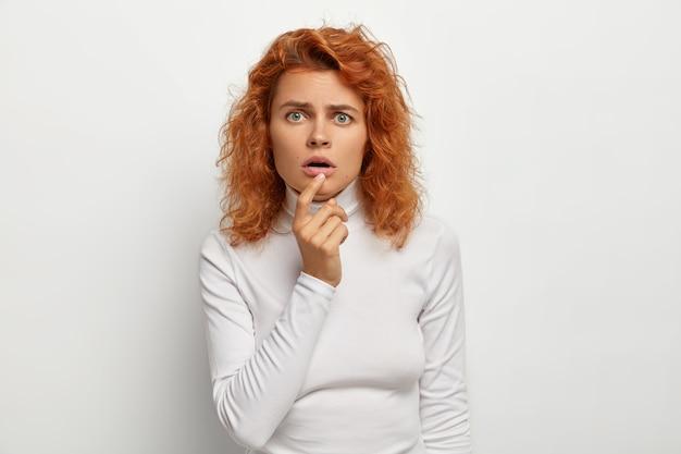 Zdziwiona Zaskoczona Młoda Kobieta Przygląda Się Uważnie Z Otwartymi Ustami, Reaguje Na Coś Niesamowitego, Ma Rude Włosy, Zielone Oczy, Nosi Swobodny Golf, Odizolowany Na Białej ścianie Darmowe Zdjęcia