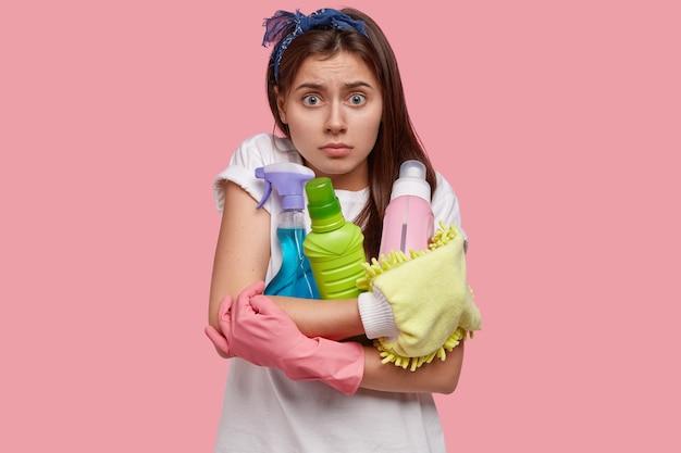 Zdziwiona Zaskoczona Piękna Kobieta Ma Przestraszony Wyraz Twarzy, Trzyma Detergenty Do Czyszczenia, Nosi Gumowe Rękawiczki, Sfrustrowana Dużą Ilością Pracy Darmowe Zdjęcia