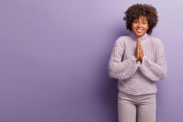 Żebrząca Urocza Afroamerykańska Dama Ma Błagalną Pogodną Twarz, Prosi O Wsparcie, Trzyma Dłonie W Modlitewnym Geście, Nosi Swobodny Zimowy Sweter, Odizolowany Od Fioletowej ściany. Darmowe Zdjęcia