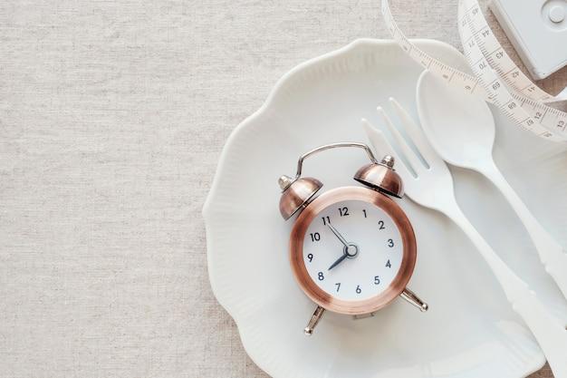 Zegar na talerzu i centymetrze, przerywana koncepcja diety na czczo Premium Zdjęcia