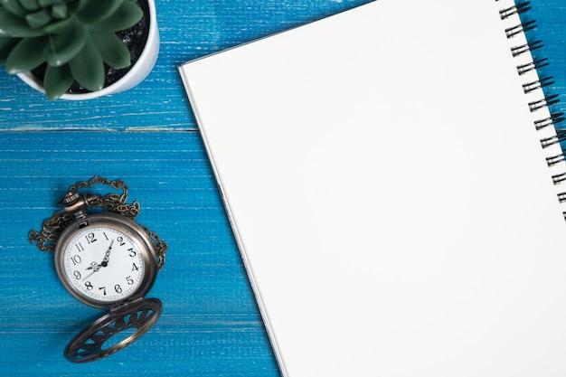 Zegarek Kieszonkowy Umieścić I Pusty Notatnik Na Niebieskim Drewnianym Stole. Premium Zdjęcia