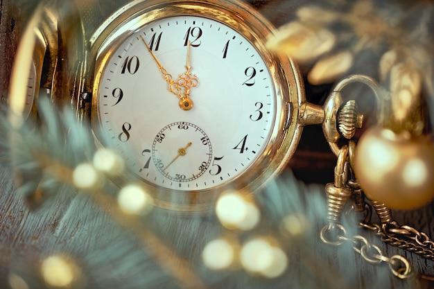 Zegarek W Stylu Vintage Przedstawiający Pięć Do Dwunastu Na Szarym Rustykalnym Z Gałązkami Jodły I Złotymi Dekoracjami Premium Zdjęcia