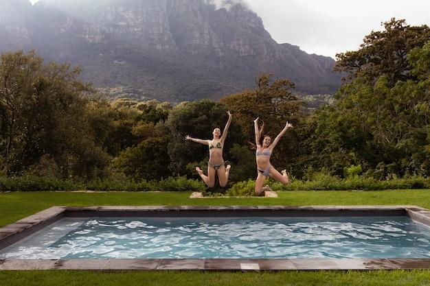 Żeńscy Przyjaciele Skacze W Pływackim Basenie Przy Podwórkiem Darmowe Zdjęcia