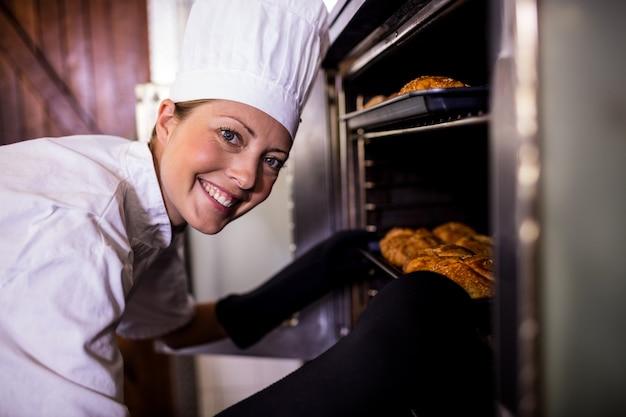 Żeńscy szefowie kuchni wkładają blachę do pieczenia rolki kaiser w piekarniku Premium Zdjęcia