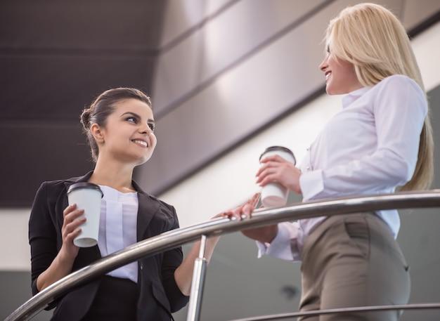 Żeńscy urzędnicy opowiada podczas przerwy na kawę. Premium Zdjęcia