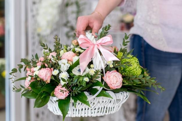 Żeńska kwiaciarnia trzyma pięknego bukiet róże w białym koszu Premium Zdjęcia