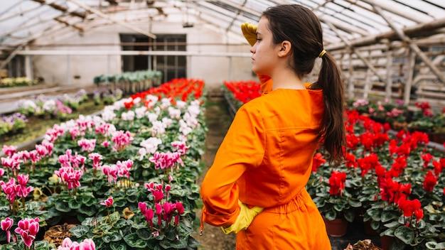 Żeńska Ogrodniczka Zasłania Jej Oczy Z Kolorowymi Kwiatami Rw Szklarni Darmowe Zdjęcia
