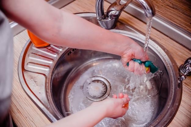 Żeńska ręka domycie naczynie gąbka z dishwashing mydłem. koncepcja czyszczenia domu. Premium Zdjęcia