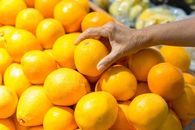 Żeńska ręka podnosi pomarańcze w supermarkecie Premium Zdjęcia