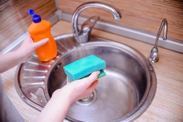 Żeńska ręka z naczynie gąbką z dishwashing mydłem. koncepcja czyszczenia domu. Premium Zdjęcia