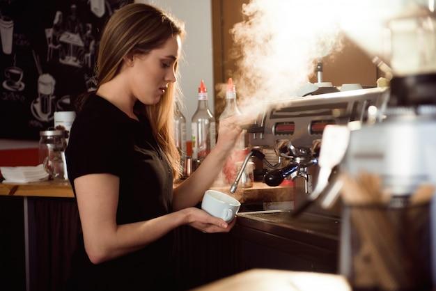 Żeński barista robi kawie w sklep z kawą kontuarze. barista kobieta pracuje w kawiarni Premium Zdjęcia