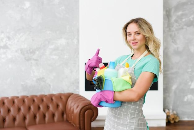 Żeński cleaner gestykuluje thumbup stoi w domu trzymać cleaning narzędzia i produkty Darmowe Zdjęcia