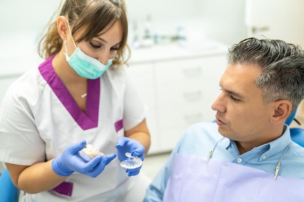 Żeński dentysta pokazuje szynę pacjentowi. Premium Zdjęcia
