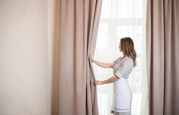 Żeński Housekeeping Chambermaid Pracownik Z Otwarcie Zasłonami Okno W Pokoju Premium Zdjęcia