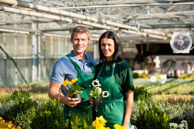 Żeński i męski ogrodnik w targowym ogródzie Premium Zdjęcia