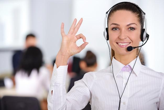 Żeński obsługa klienta operator z słuchawki i ono uśmiecha się. Premium Zdjęcia