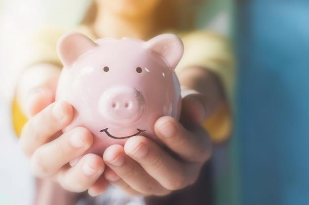 Żeński ręki mienia prosiątka bank. oszczędź pieniądze i inwestycje finansowe Premium Zdjęcia