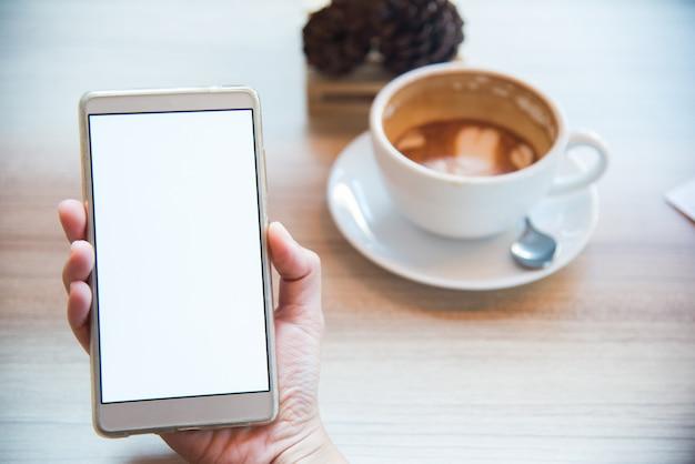 Żeński używa smartphone, zakończenie, filiżanka na tle Premium Zdjęcia