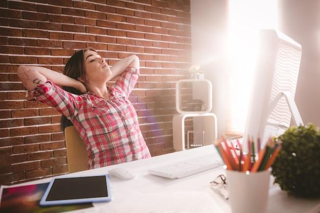 Żeński wykonawczy relaksować przy jej biurkiem Premium Zdjęcia