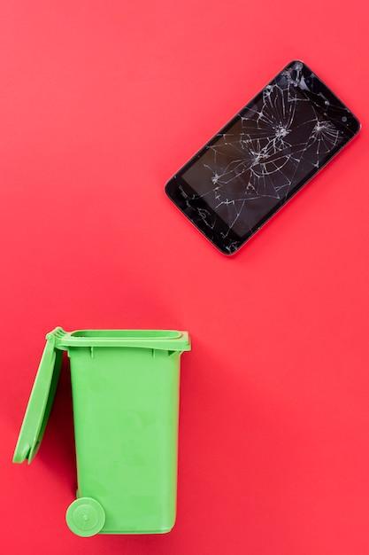 Zepsuty Ekran Telefonu Komórkowego I Zielony Kosz Na śmieci. Recykling. Premium Zdjęcia