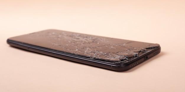 Zepsuty Telefon Na Beżowym Tle Zbliżenie Rozbite Szkło Wyświetlacz Smartfona. Premium Zdjęcia