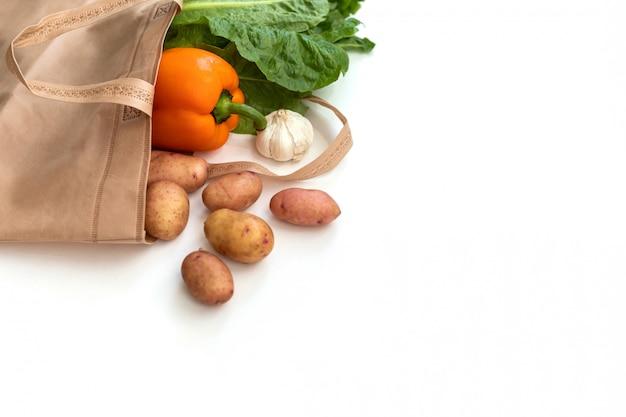 Zero odpadów zużywa mniej plastiku świeże warzywa organiczne w workach z eko-bawełny na drewnianym stole biała torba z płótna z wolnej przestrzeni na zakupy z tworzyw sztucznych Premium Zdjęcia