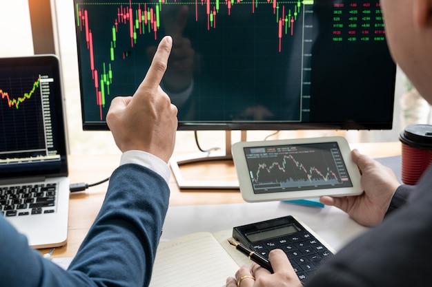 Zespół biznesowy inwestor przedsiębiorca handel omawianie i analiza danych na wykresach giełdowych. Premium Zdjęcia