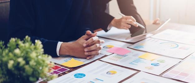 Zespół firmy za pomocą tabletu działa na stole i dokumentów finansowych w biurze. Premium Zdjęcia