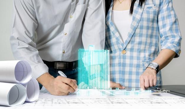 Zespół Inżynierów Pracuje Nad Projektem Modelu Budynku Opartego Na Technologii Wyświetlania Planu Arkusza Premium Zdjęcia