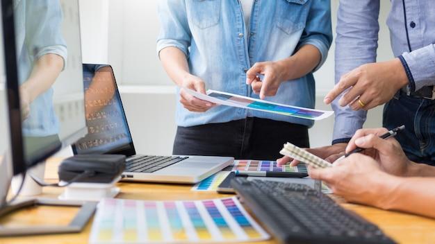 Zespół projektantów graficznych pracujących nad projektowaniem stron internetowych za pomocą próbek kolorów do edycji grafiki przy użyciu tabletu i rysika na biurku w biurze kreatywnym. Premium Zdjęcia