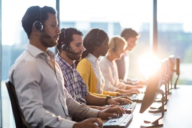 Zespół Współpracowników Pracujących Przy Biurku Z Zestawu Słuchawkowego Premium Zdjęcia