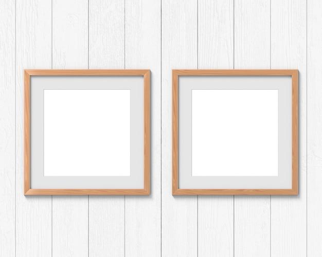 Zestaw 2 Kwadratowych Makiet Drewnianych Ram Z Ramką Wiszącą Na ścianie. Puste Miejsce Na Zdjęcie Lub Tekst. Renderowanie 3d. Premium Zdjęcia