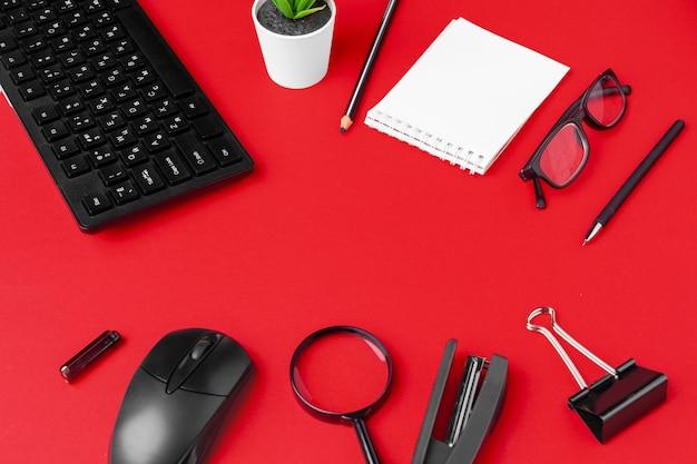 Zestaw artykułów piśmiennych na czerwonym biurku Premium Zdjęcia