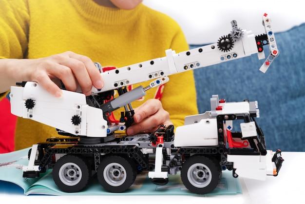 Zestaw do montażu samochodów, kobieta montuje bardzo skomplikowaną i popularną zabawkę samochodzik. Premium Zdjęcia