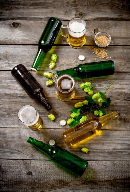 Zestaw Do Piwa. Butelki I Szklanki Piwa, Słodu I Zielonego Chmielu Na Drewnianym Stole. Widok Z Góry Premium Zdjęcia