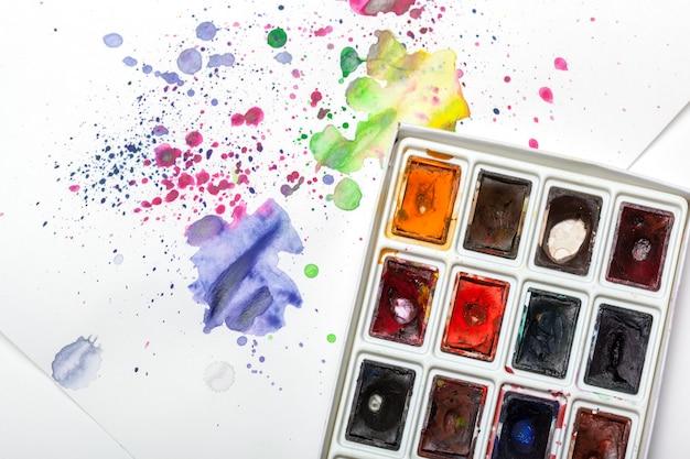 Zestaw farb akwarelowych z próbkami rozpryski farby na papierze Premium Zdjęcia