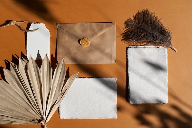 Zestaw Kart Z życzeniami Z Białego Papieru Akwarelowego Z Liściem Palmowym, Piórkiem Strusia, Kopertą Rzemieślniczą Na Teksturowanym Stole Z Terakoty. Elegancki Nowoczesny Szablon. Leżał Płasko, Widok Z Góry Premium Zdjęcia