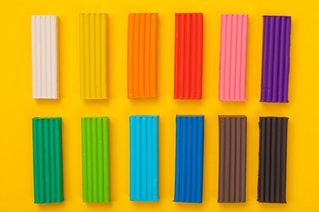 Zestaw kolorowych plasteliny na białym tle na żółtym tle Premium Zdjęcia