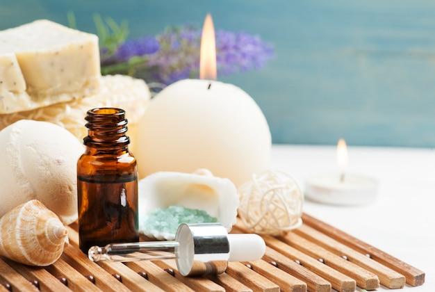 Zestaw łazienkowy spa z olejkiem eterycznym, solą, bombą, mydłem i zapalonymi świecami. koncepcja masażu, relaksu i aromaterapii Premium Zdjęcia