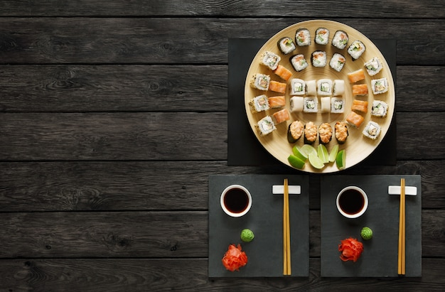 Zestaw Maki Do Sushi I Roladki Na Czarnym Rustykalnym Drewnie Premium Zdjęcia