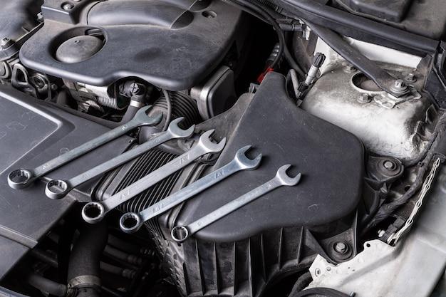 Zestaw Metalowych Kluczy Różnej Wielkości Leży Pod Maską Samochodu Na Chłodnicy Oleju. Pojęcie Naprawy Samochodu I Narzędzi W Serwisie Samochodowym Premium Zdjęcia
