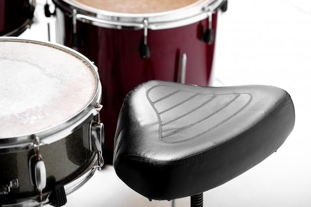 Zestaw Perkusyjny Na Białym Zestaw Instrumentów Muzycznych I Czarne Krzesło Premium Zdjęcia