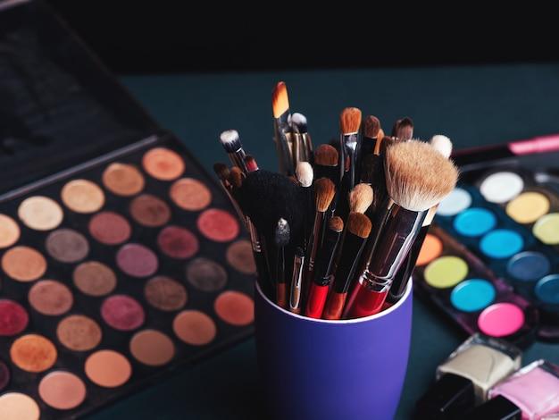Zestaw Profesjonalnych Pędzli Do Makijażu Na Tle Palety Z Kolorowymi Cieniami Do Powiek I Kosmetykami Premium Zdjęcia